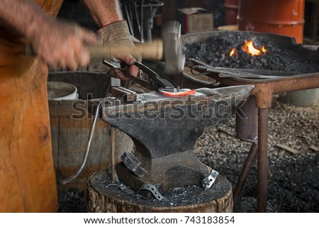 Blacksmith Hammers on Horseshoe - motion blur