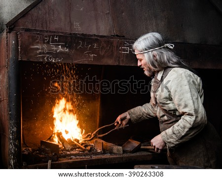 Blacksmith heats item before forging - stock photo