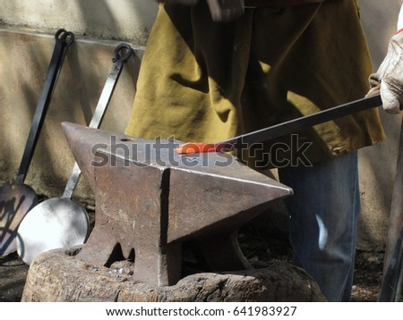 Blacksmith manually forging the molten metal with hammer on the anvil . Photo taken during outdoor public event (no ticket required) in public place . Pistoia, Italy