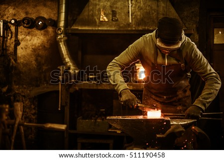 Blacksmith with brush handles the molten metal on the anvil in smithy.