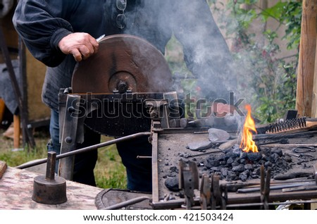 Blacksmith working on metal medieval - stock photo