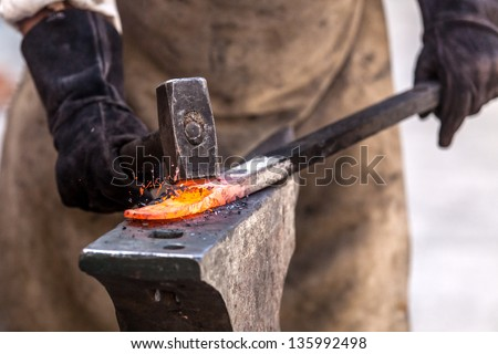 Blacksmith working on metal on anvil at forge high speed detail shot - stock photo