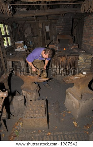 Blacksmith working with metal in old workshop
