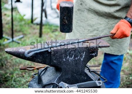 blacksmith works on an anvil. - stock photo