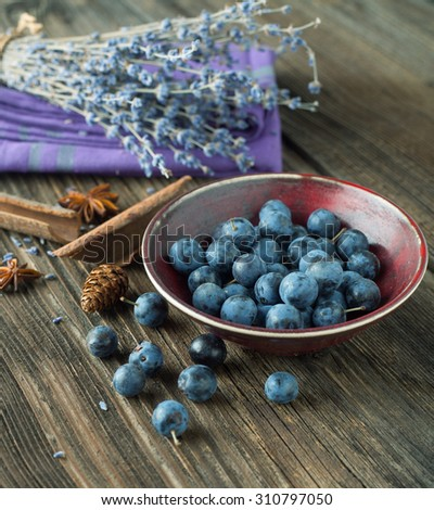 Blackthorn in a bowl on a wooden table - stock photo