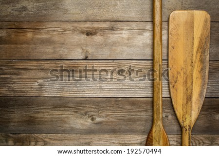 blade and grip of wooden canoe paddle against rustic wood background with a copy space - stock photo