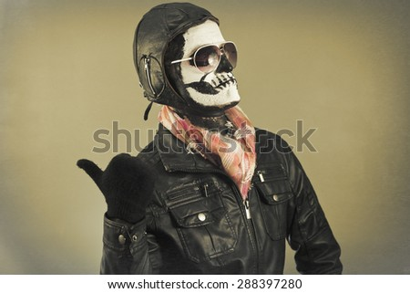 Blaming aviator with face painted as human skull