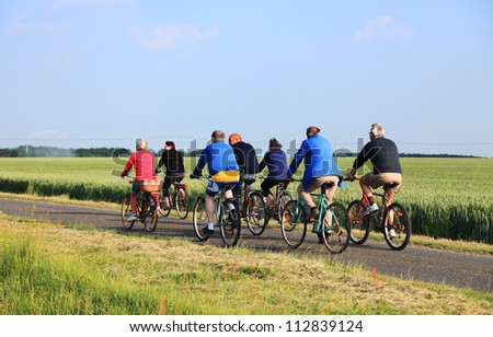 BLANDAINVILLE, FRANCE JUNE 2: Senior people ride their bicycles on a lane between wheat fields on June 2, 2010 in Blandainville, France.Riding bicycles is a common activity in France. - stock photo