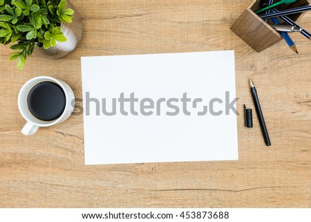 Blank A4 paper on the wood desk table with coffee and pen. Top view, flat lay. - stock photo