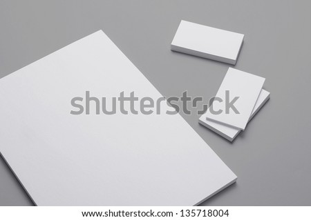 Blank A4 print paper and Business cards isolated on grey background with soft shadows / Stationary - stock photo