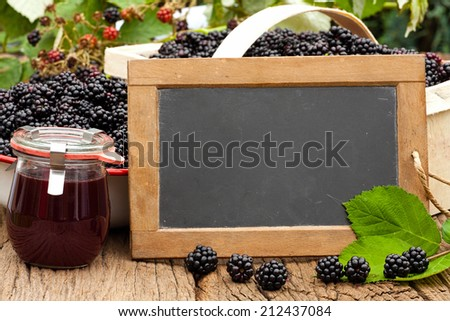 Blank advertising space on a slate blackboard in front of ripe blackberries and a on a rustic wooden table - stock photo