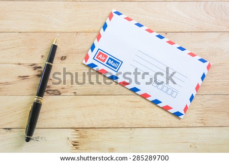 Blank airmail envelope with pen on wood table background - stock photo