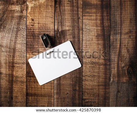 Blank badge. Blank plastic id card on vintage wooden table background. Blank white plastic badge. Mock-up for branding identity. Top view. - stock photo