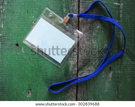 Blank badge with neckband on a wooden background