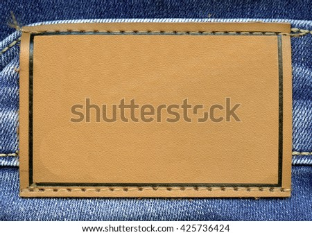 blank beige leather label on jeans background