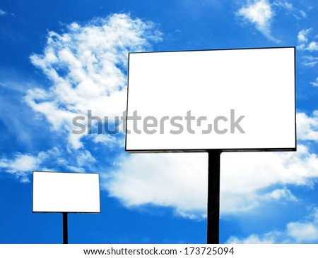 Blank billboard against blue sky with clouds.