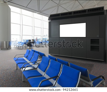blank billboard and blue chair waiting room at a international airport with busy traveler - stock photo