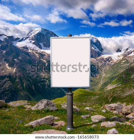 blank billboard for advertising mounted on a meadow among the mountains with snow-capped peaks