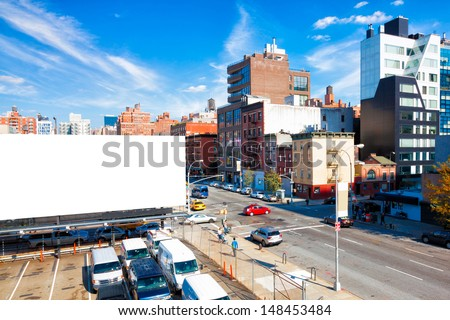 Blank billboard in a city with high rise buildings and a bright blue sky overhead - stock photo