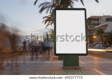 Blank billboard in a footpath at sunset, with blurred people walking