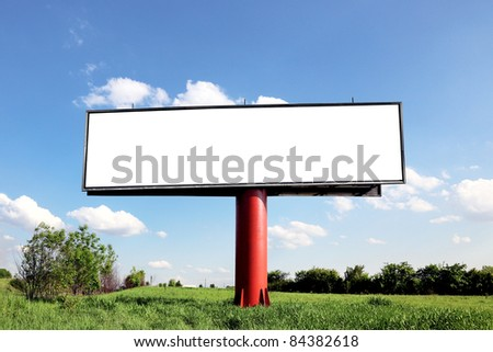 Blank billboard on a field with the blue sky