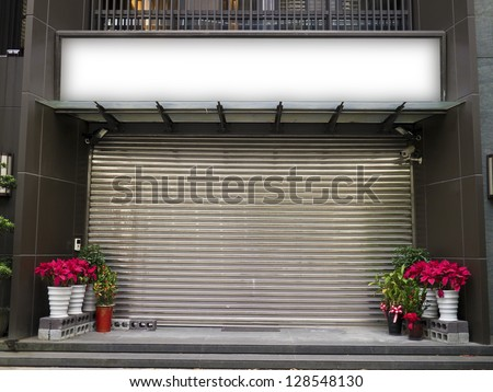 blank billboard on the wall of a closed store - stock photo