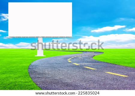 Blank billboard ready for new advertisement and asphalt road on green grass field representing the concept of journey to a focused destination resulting to success  - stock photo