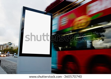 Blank billboard with copy space for your text message or promotional content, public information board in city with with blurred bus on background, empty advertising mock up banner on roadway - stock photo