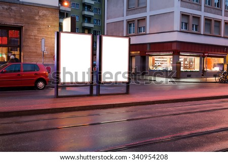 Blank billboards on bus stop at night - stock photo