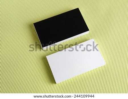 Blank black and white business cards on a green background. - stock photo