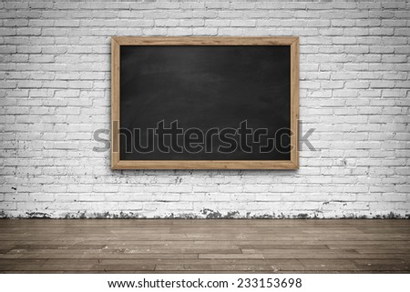 Blank black chalkboard in wooden frame on brick wall with wooden floor. Background and texture. - stock photo