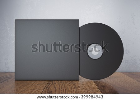 Blank black compact disk with cover on wooden table and concrete wall background. Mock up, 3D Rendering