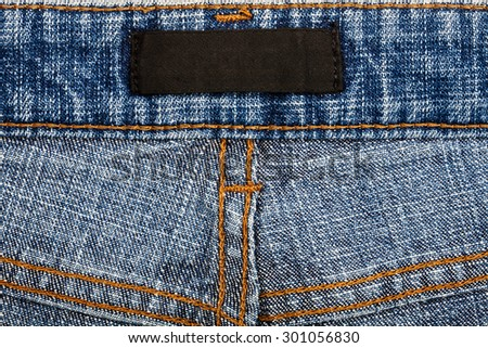 Blank black fabric jeans inner label sewed on a blue jeans. - stock photo