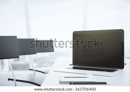 Blank black laptop screen on white table in conference room with chairs and big windows