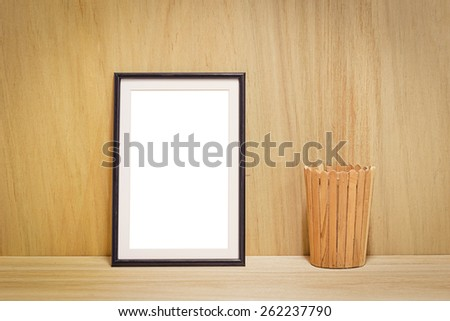blank black picture frame and wooden bucket on the wooden background - stock photo