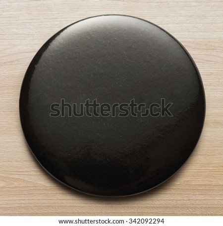 Blank black round badge on wooden background - stock photo