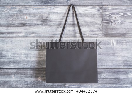 Blank black shopping bag hanging on wooden wall. Mock up - stock photo