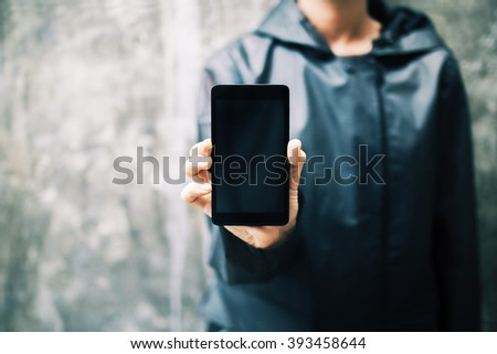 Blank black smartphone held by a girl in a dark blue hoodie on concrete background. Mock up