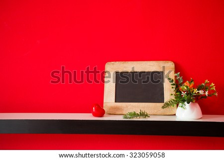 blank blackboard and Vase of flowers  on the red wall copy space  - stock photo