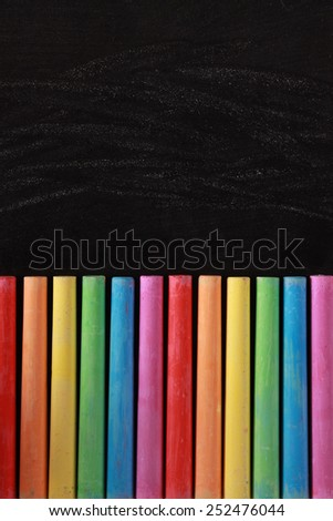 Blank blackboard background with some colorful chalks. - stock photo