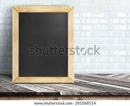 Blank blackboard on tropical wooden table at white tile wall,Template mock up for adding your design and leave space beside frame for adding more text - stock photo