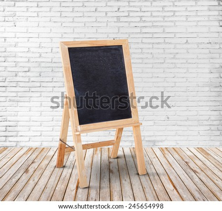 Blank blackboard on wood floor and white brick wall background - stock photo