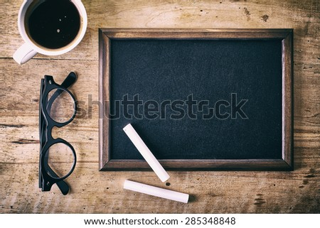 Blank blackboard with a piece of chalk, glasses and coffee on wooden background - stock photo