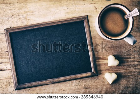 Blank blackboard with candy hearts and cup of coffee on wooden background - stock photo