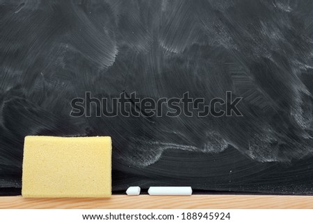 Blank blackboard with chalks and eraser - stock photo