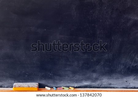 Blank blackboard with colored chalks and eraser. Horizontal composition. - stock photo
