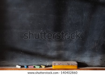 Blank blackboard with colored chalks and eraser. Horizontal composition and with Light and Shadows Effect