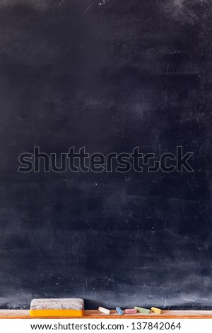 Blank blackboard with colored chalks and eraser. Vertical composition. - stock photo