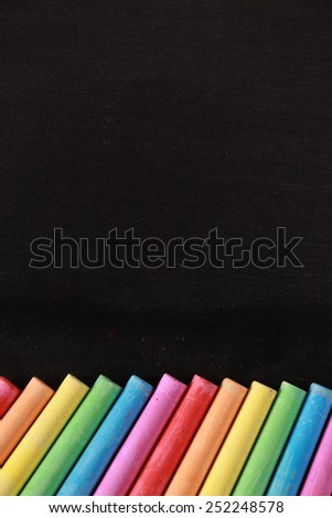 Blank blackboard with some colorful chalks. - stock photo