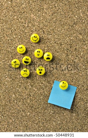 Blank blue note on corkboard with yellow thumb tacks - stock photo